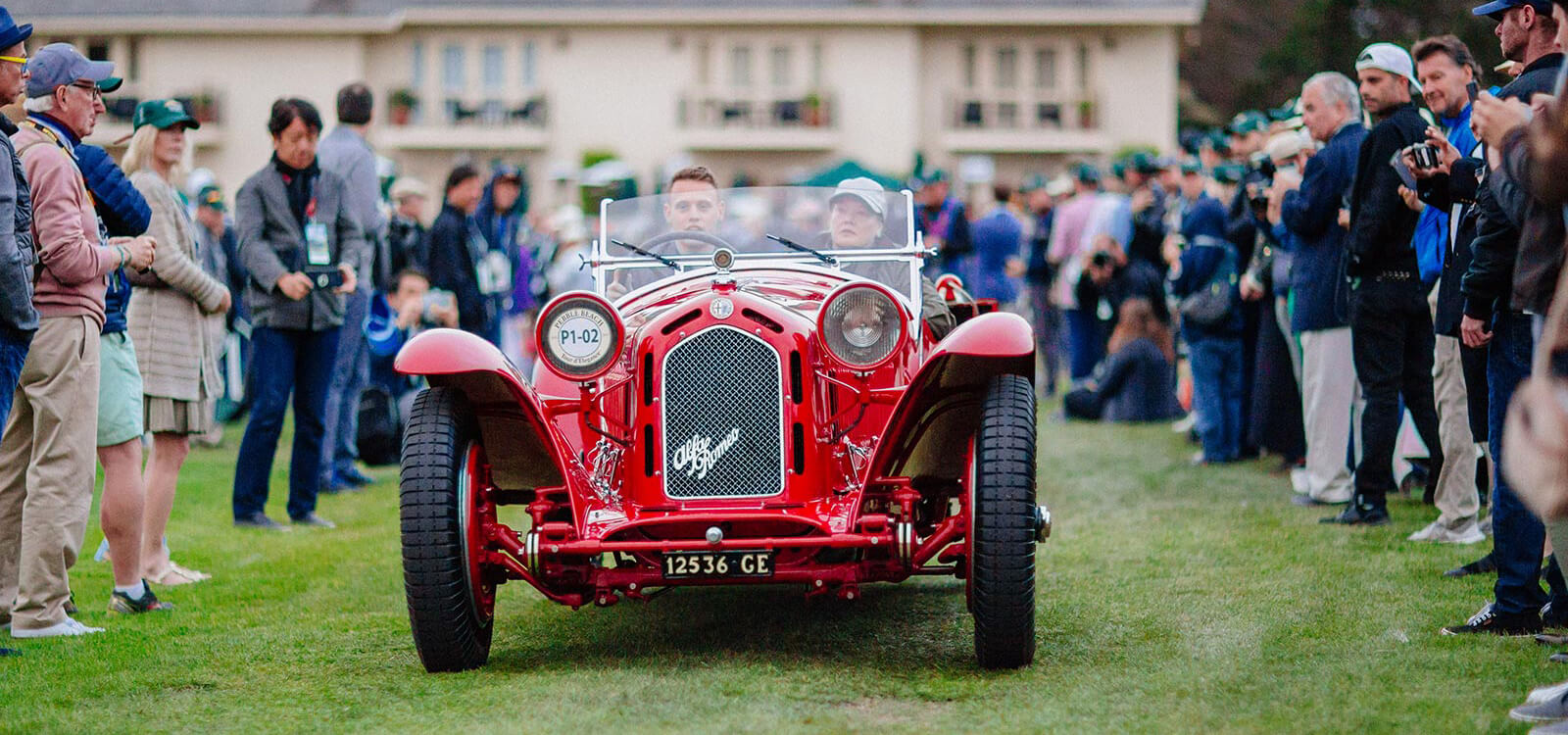 A red Alfa Romeo driving onto the show field at Dawn Patrol presented by Hagerty