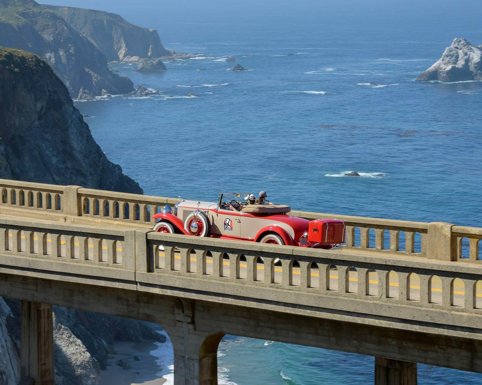 The Pebble Beach Tour d'Elegance driving across the Bixby Bridge in Big Sur, CA.