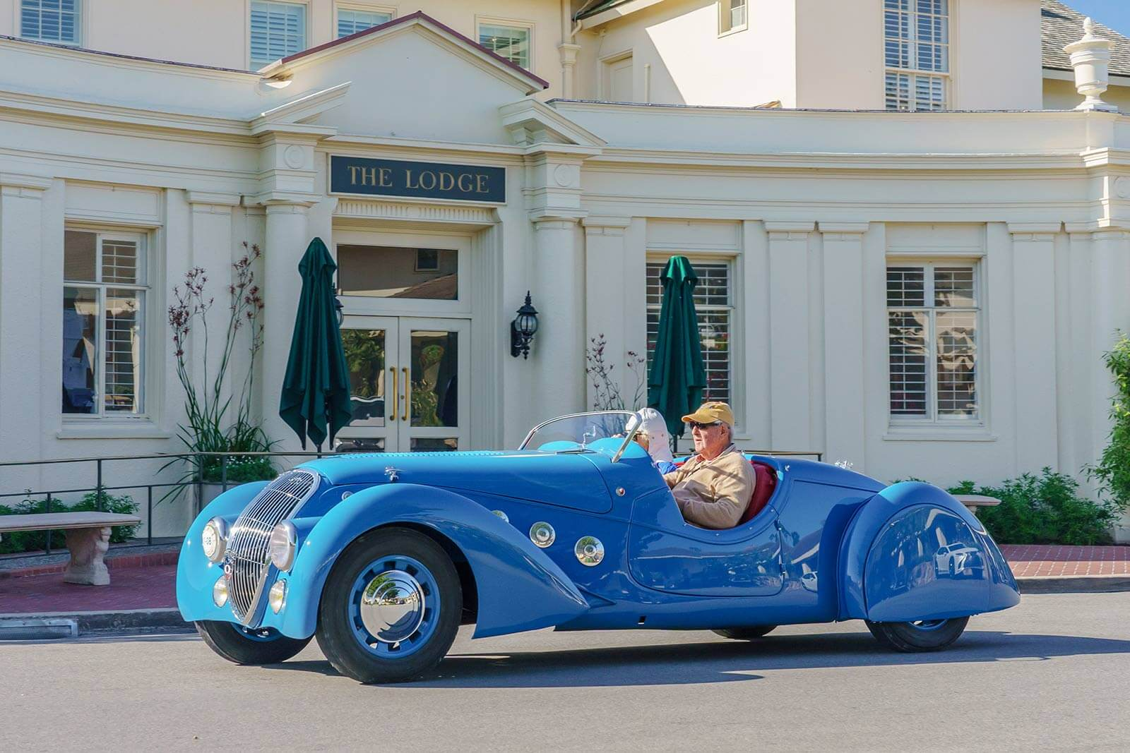 The Pebble Beach Tour d'Elegance drives past The Lodge at Pebble Beach.