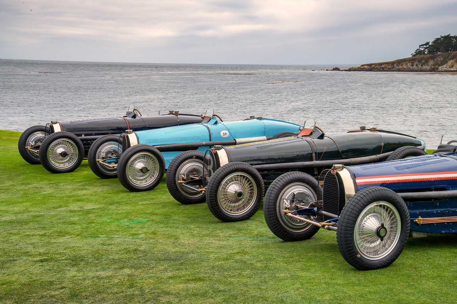 Four Bugattis lined up along the water at the Pebble Beach Concours d'Elegance